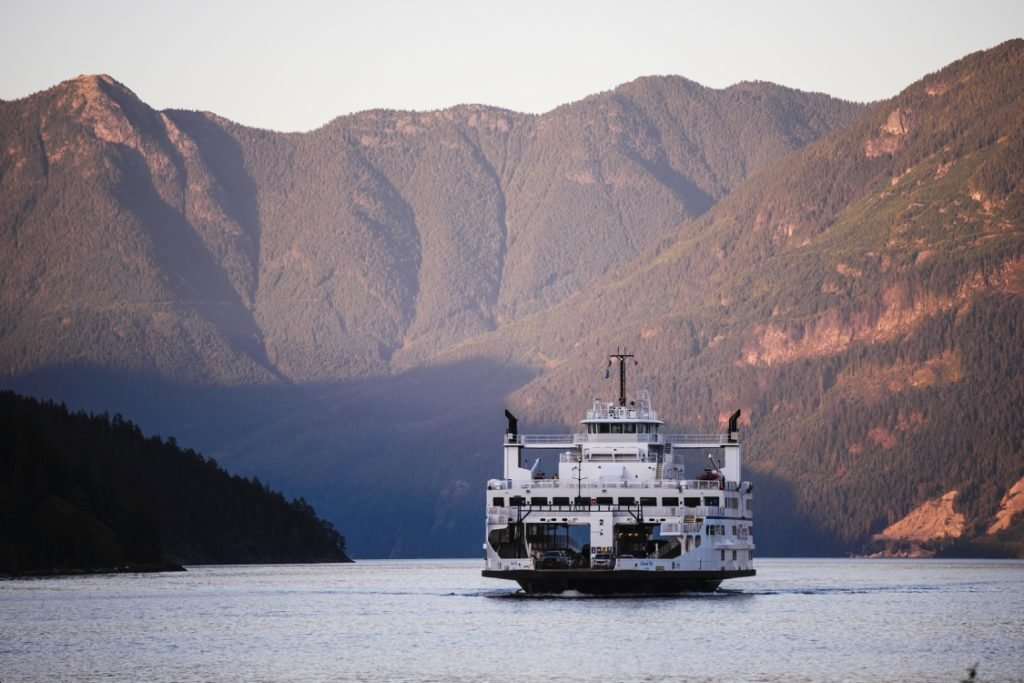 A ferry sails down a mountain surrounded river.