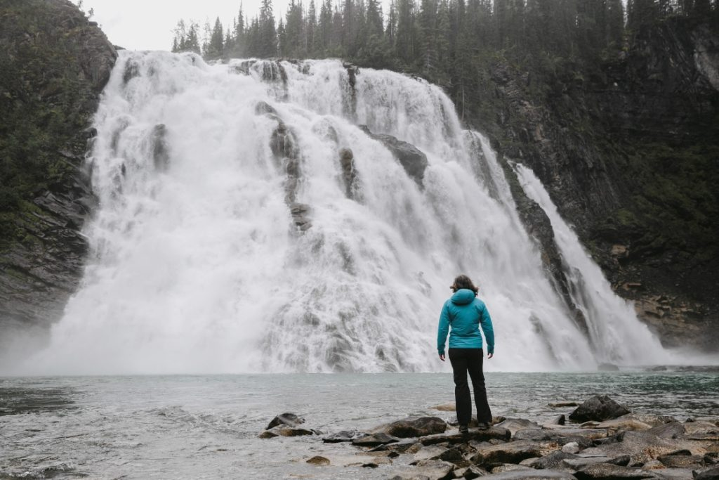 A person standing on the shore just before a large waterfall.