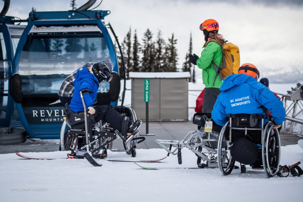 Two skiers with mobility issues in adaptive ski gear