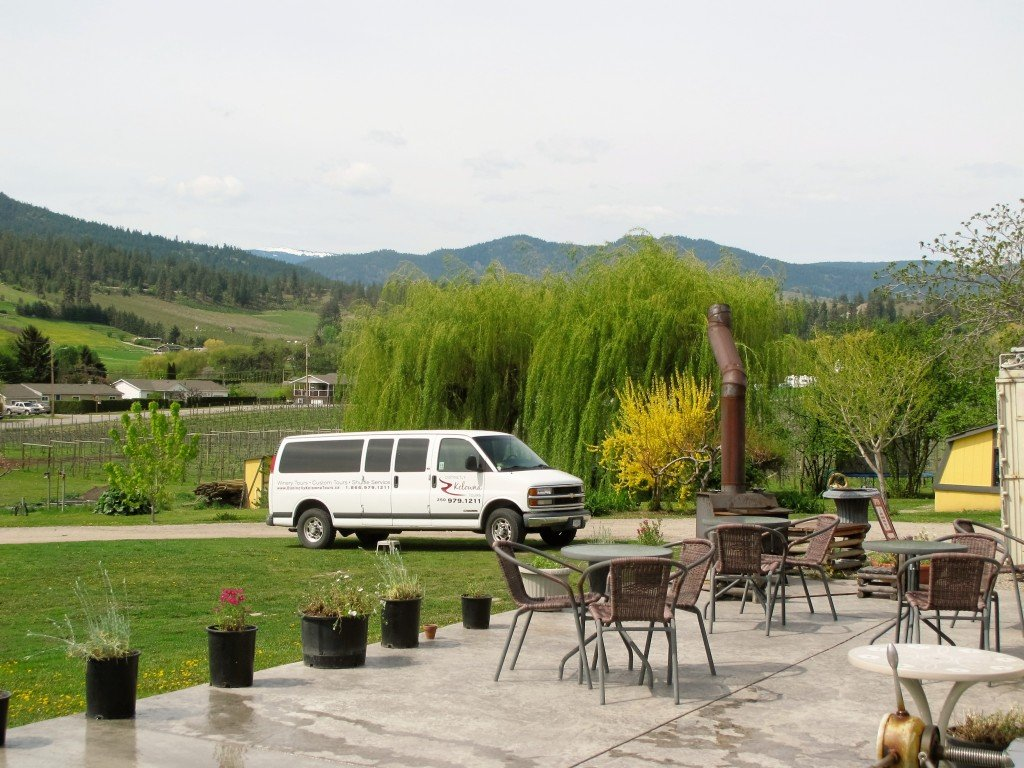 A shuttle van is parked in the driveway of a winery.