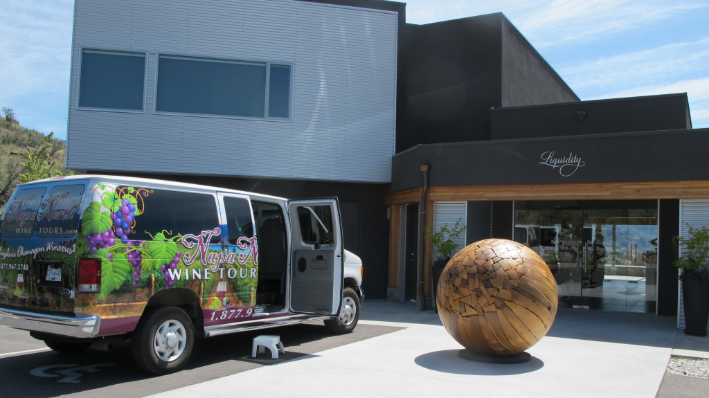 A colourfully painted tour van is parked next to a large sphere made of solid wood outside a winery.