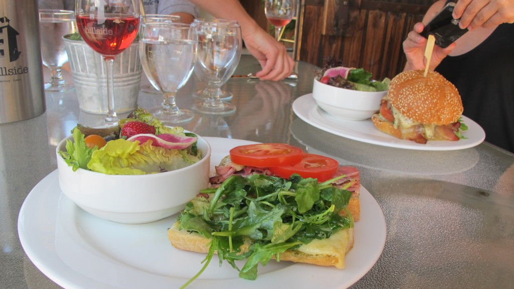 A table set for lunch with an open face sandwich and a salad on one plate, and a burger and a salad on a second plate.