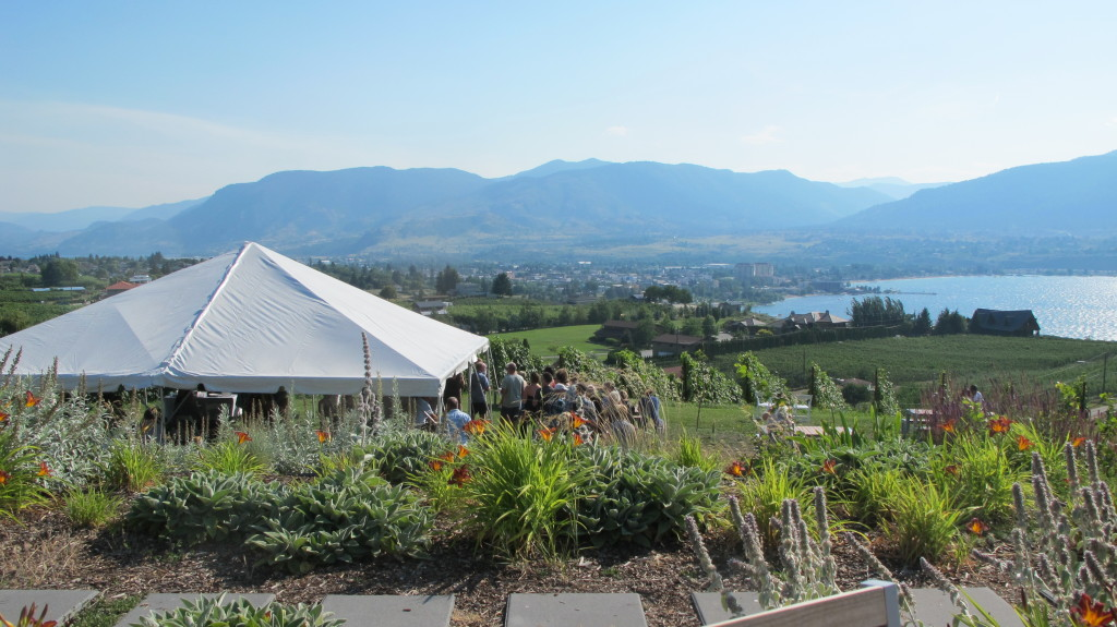 A white tent and a group of people stand on a lush lawn with views of the water and mountains.