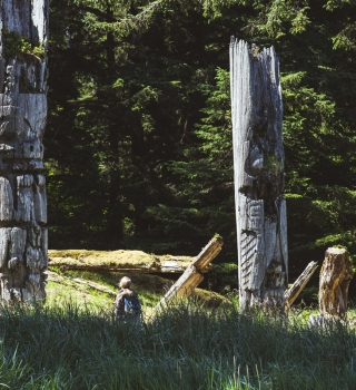 Woman in Haida Gwaii forest with totem poles
