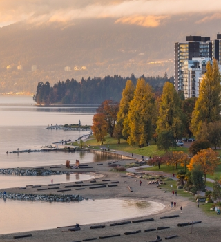 Beach front in Vancouver with mountains and buildings in the background