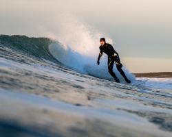Haida carver Gwaliga Hart surfing at North Beach in Naikoon Provincial Park. | Marcus Paladino