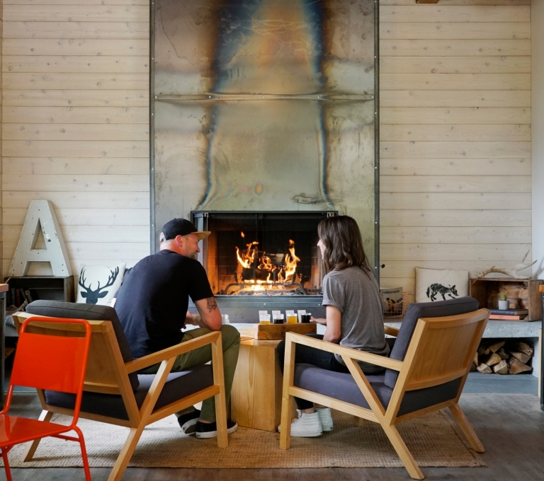 Two people enjoying craft beer in front of the fire at Field House Brewing   BC Ale Trail