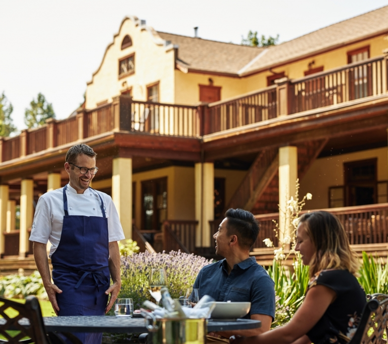 Chef Ned Bell describes the meal to a couple dining on the patio at the Naramata Inn | Hubert Kang
