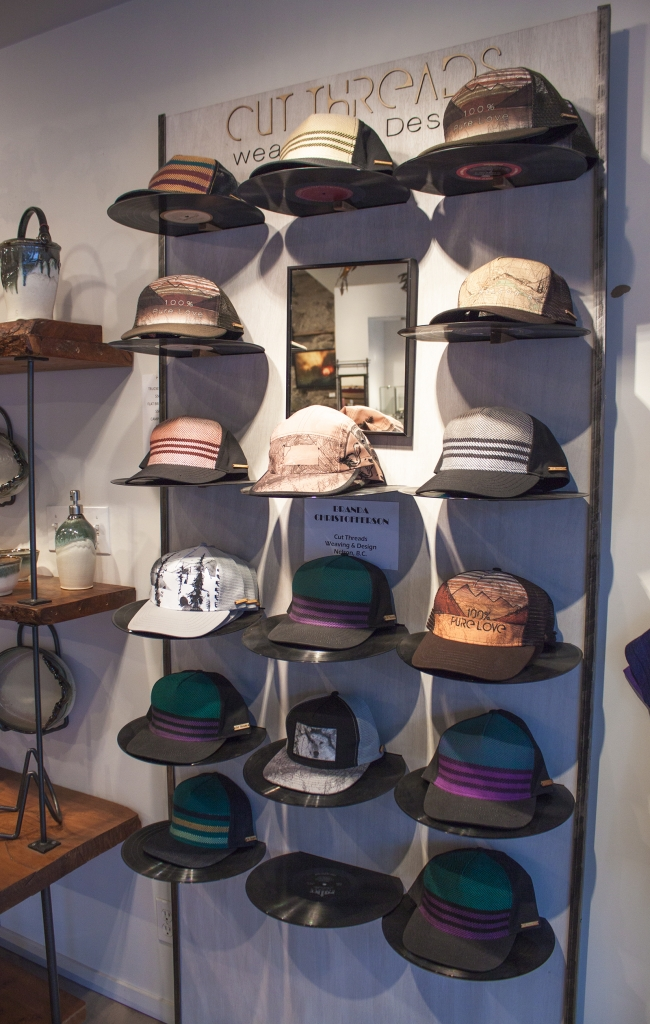 Custom trucker caps on wall of Cut Threads in Nelson, BC.