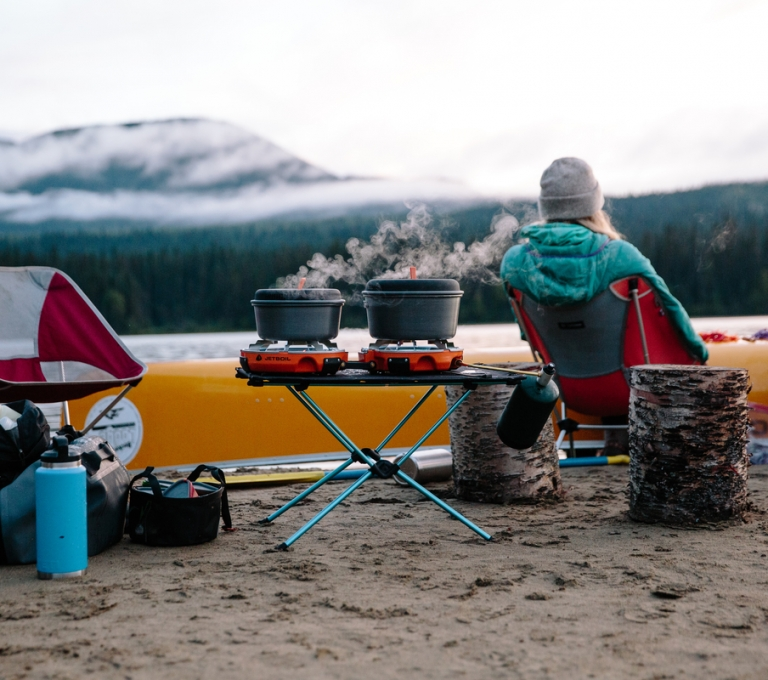 Campers cooking and camping along the banks in Bowron Lake Provincial Park | Adam Wells