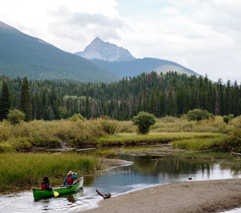 Canoers paddling through banks in Bowron Lake Provincial Park | Adam Wells
