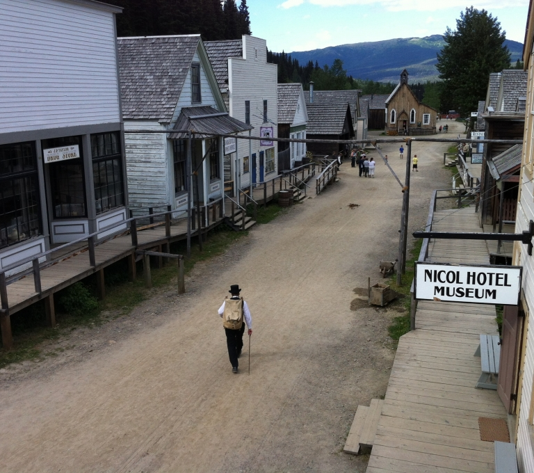 A man in period costume walks down a street of heritage buildings at Barkerville Historic Town | Destination BC