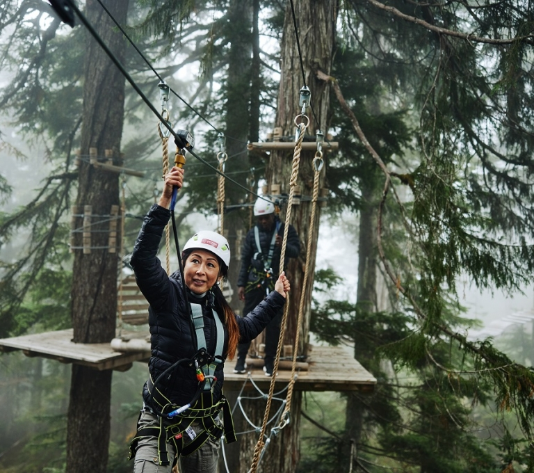 Woman ziplining at Grouse Mountain | Hubert Kang