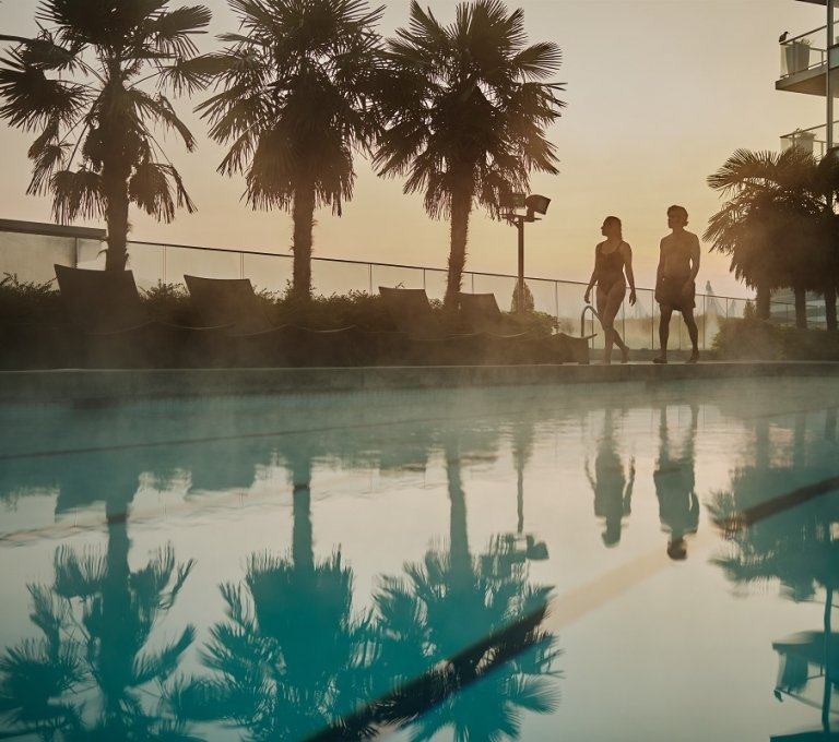 Couple by the pool at the Fairmont Pacific Rim Hotel | Hubert Kang