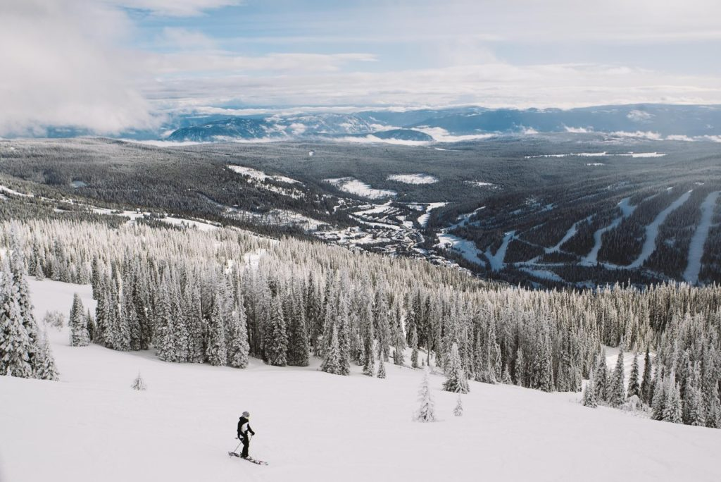 A skier stops to take in the view of Sun Peaks Resort Village.