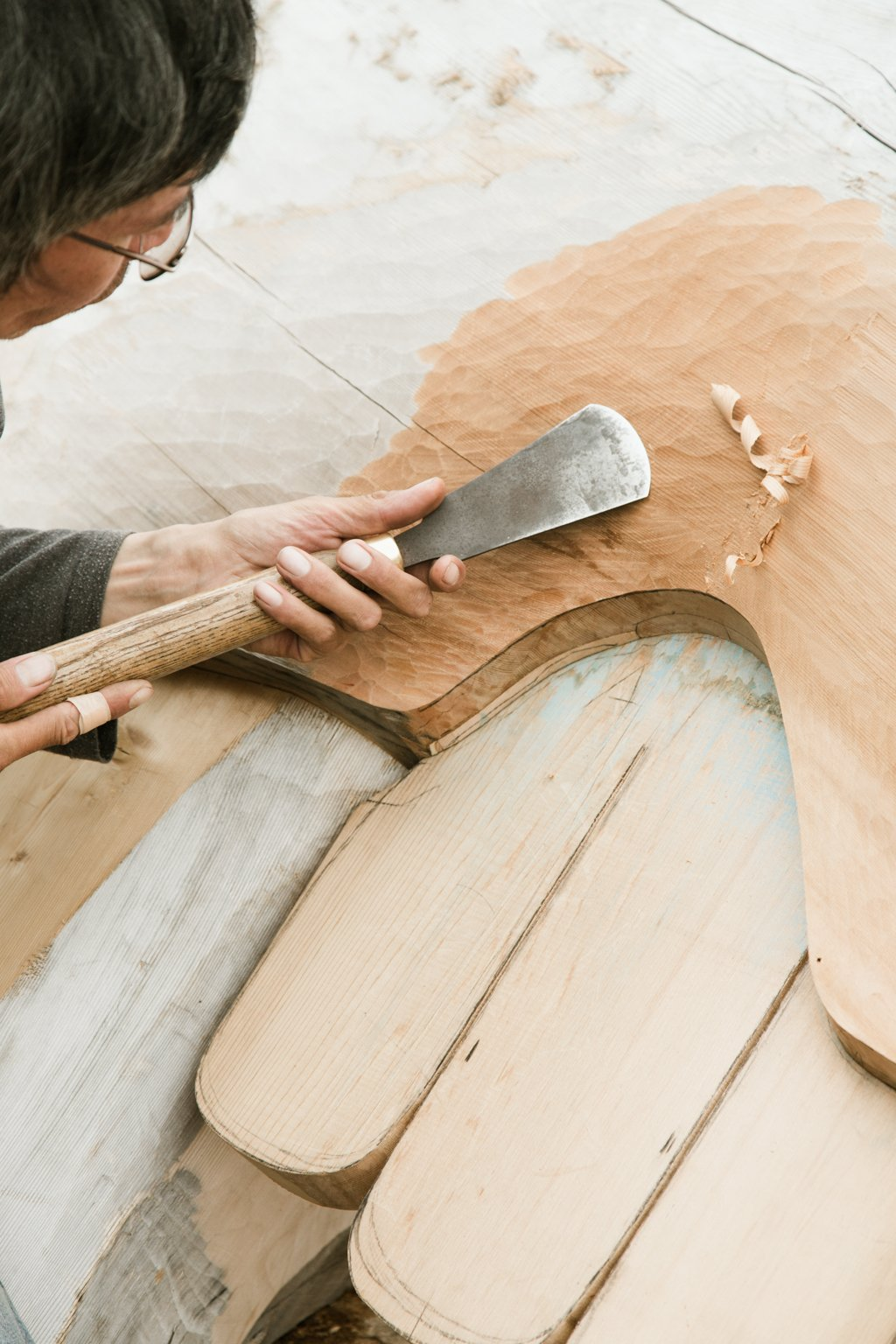 An artist carves a large piece of wood.