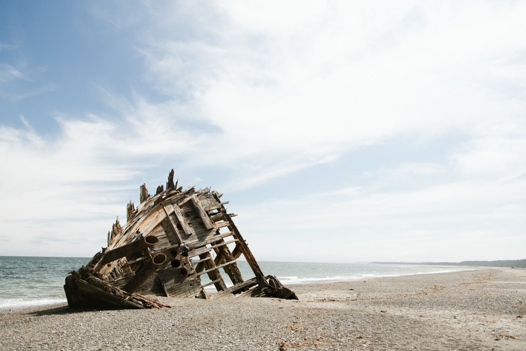 A shipwreck that has washed ashore on a beach.