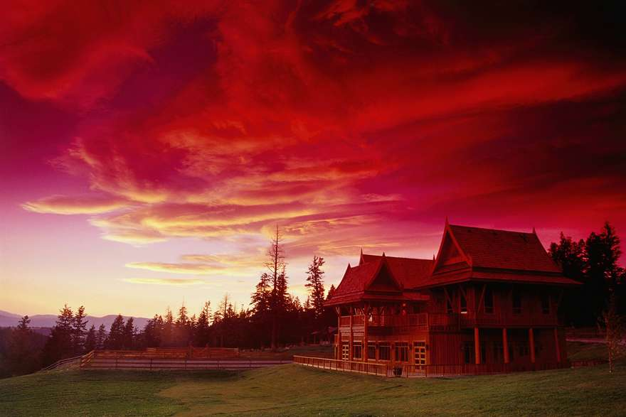 A stunning red sunset over a sprawling ranch.