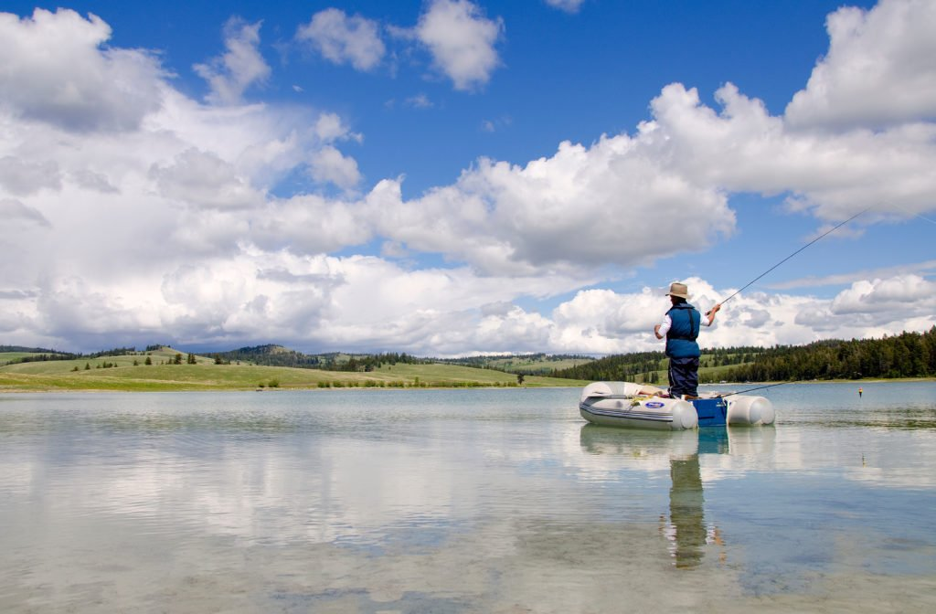 A man stands up in an inflatable dinghy, fly-fishing on a calm pond.