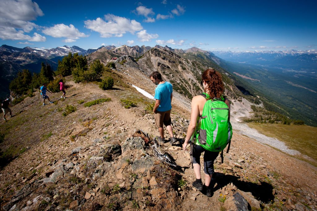 Hikers traverse a rocky terrain on a sunny day.