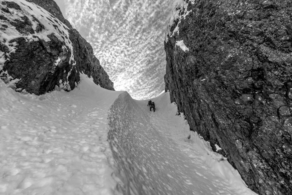 Hikers traverse a snow-filled landscape.