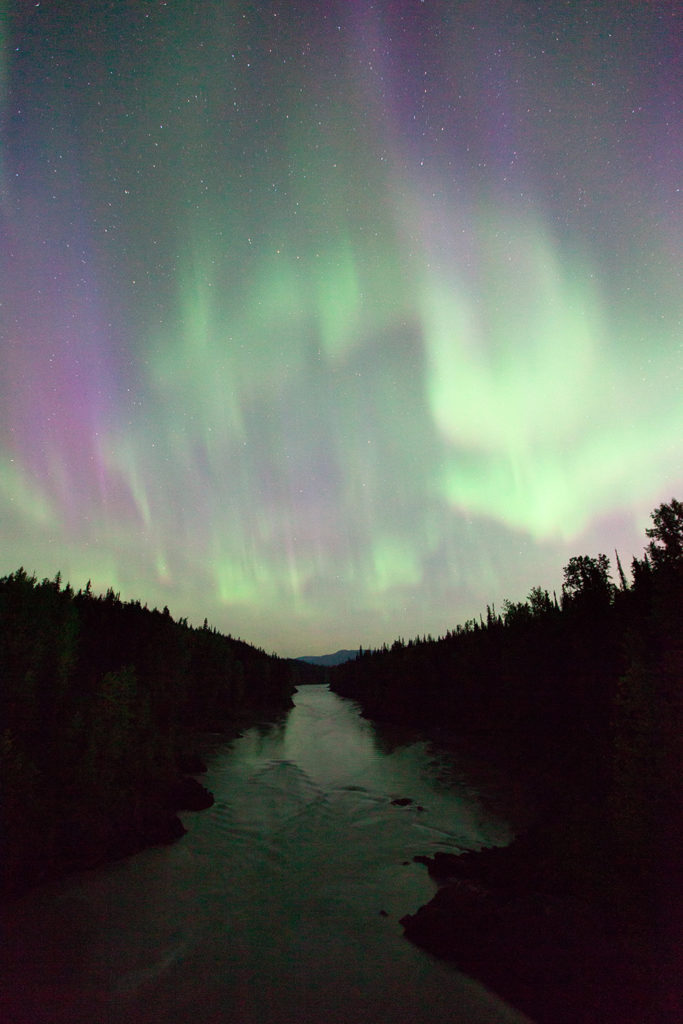 The Aurora Borealis (Northern Lights) fill the sky over the Nass River, north of Terrace, BC.