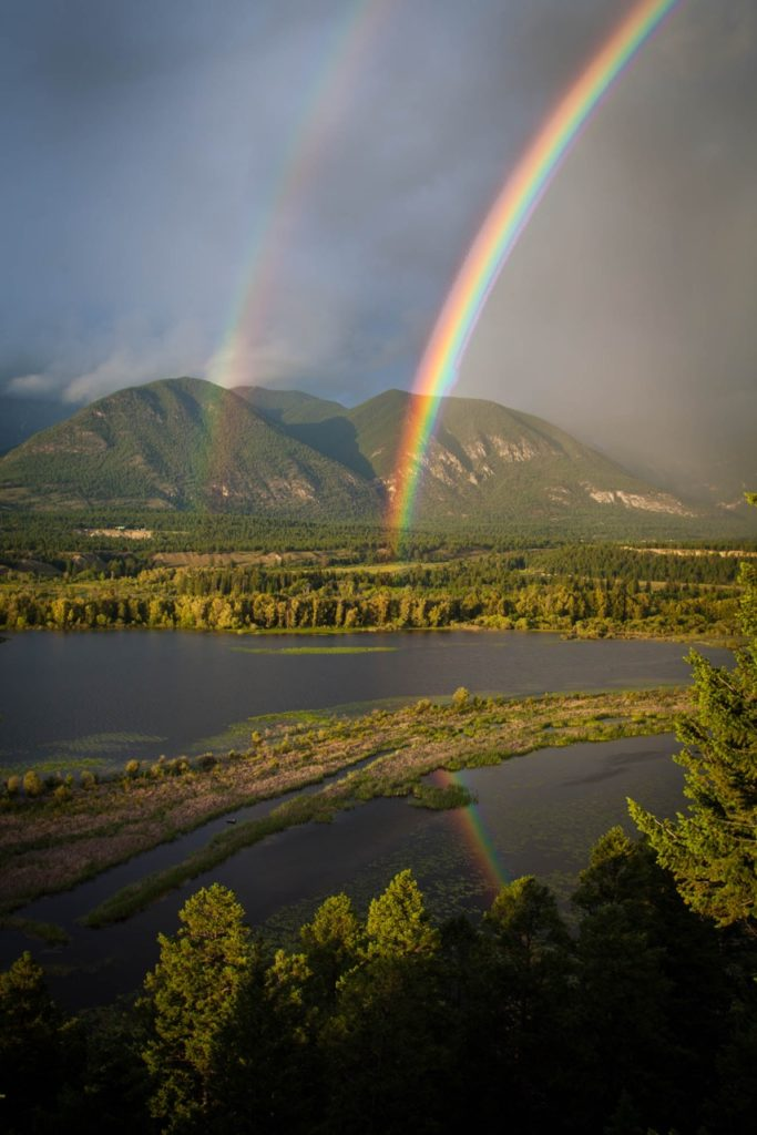 Aerial view of the lush Columbia Valley, featuring two stunning rainbows.