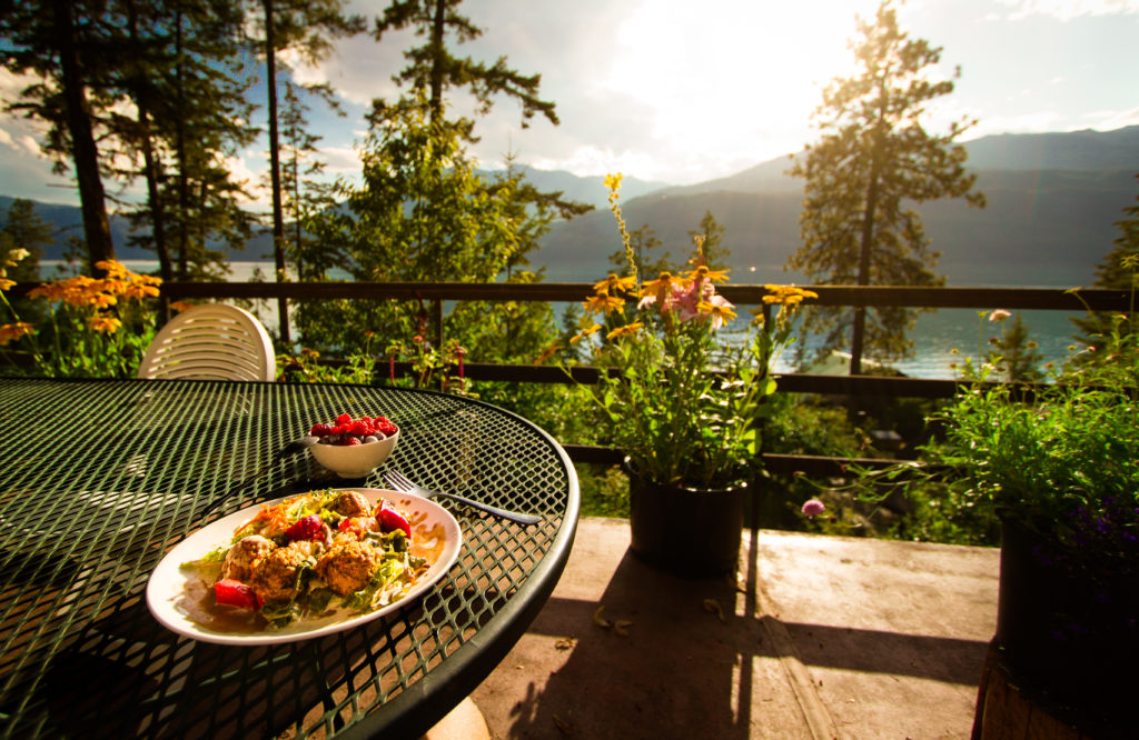 A colourfully plated salad is placed on an outdoor table with views of the mountains.
