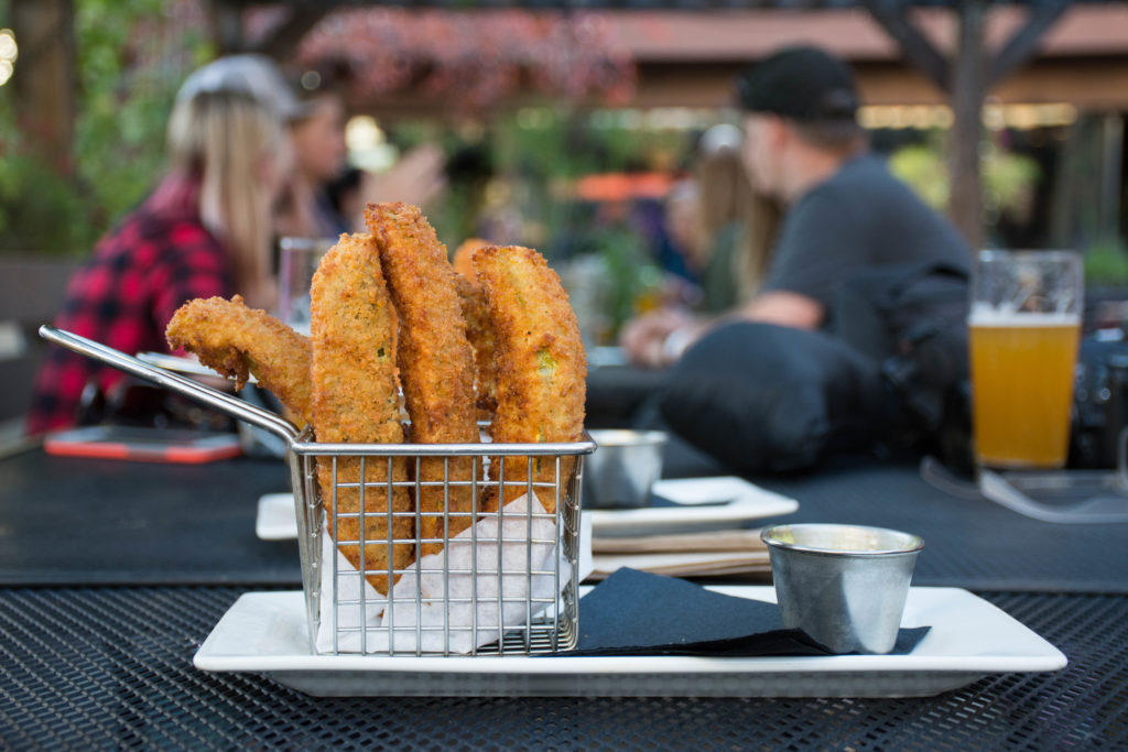 A basket of deep fried pickles sits on a table at an outdoor dining area.