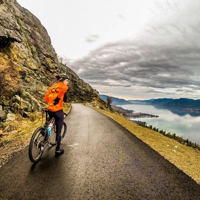 A cyclist stops to take in the view of the ocean on the Kettle Valley Trail.