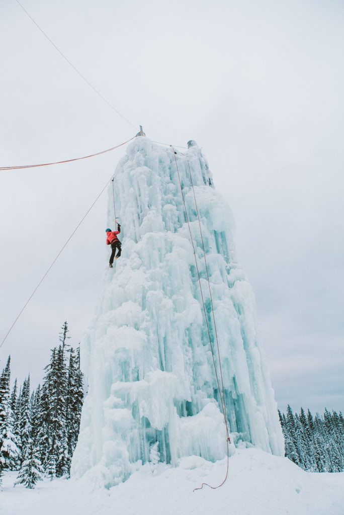 An ice climber scales a large wall of turquoise ice.