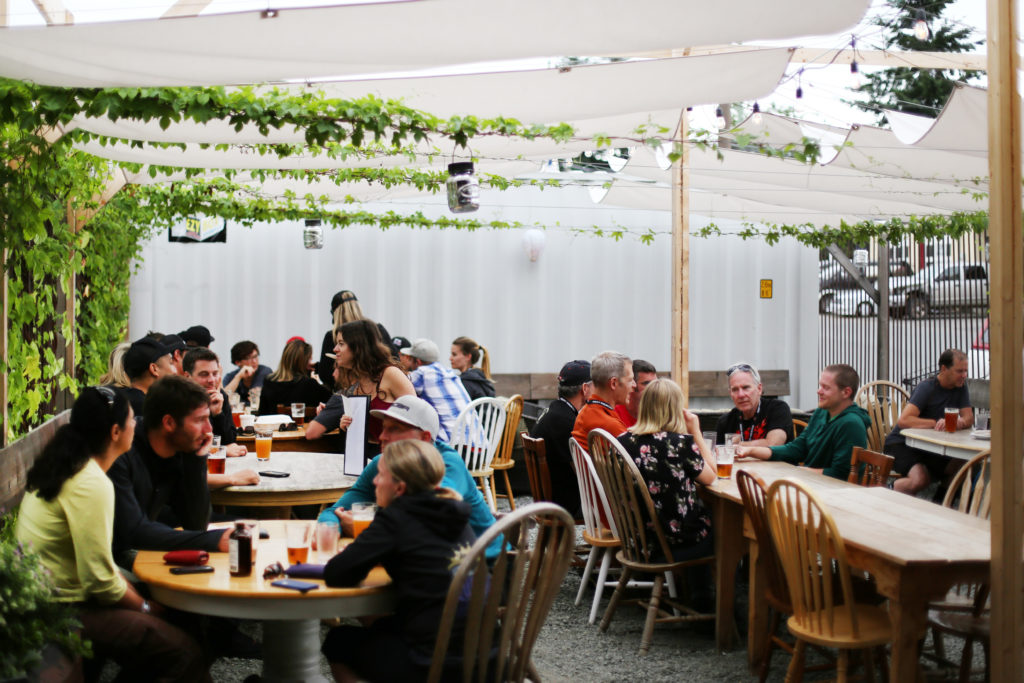 People sit at tables under a white tent, enjoying pints of craft beer.