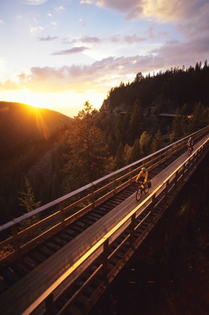 Two cyclists travel across a bridge at sunset.