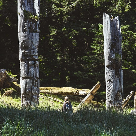 A hiker pauses to look at intricate carvings on two tall wooden poles.