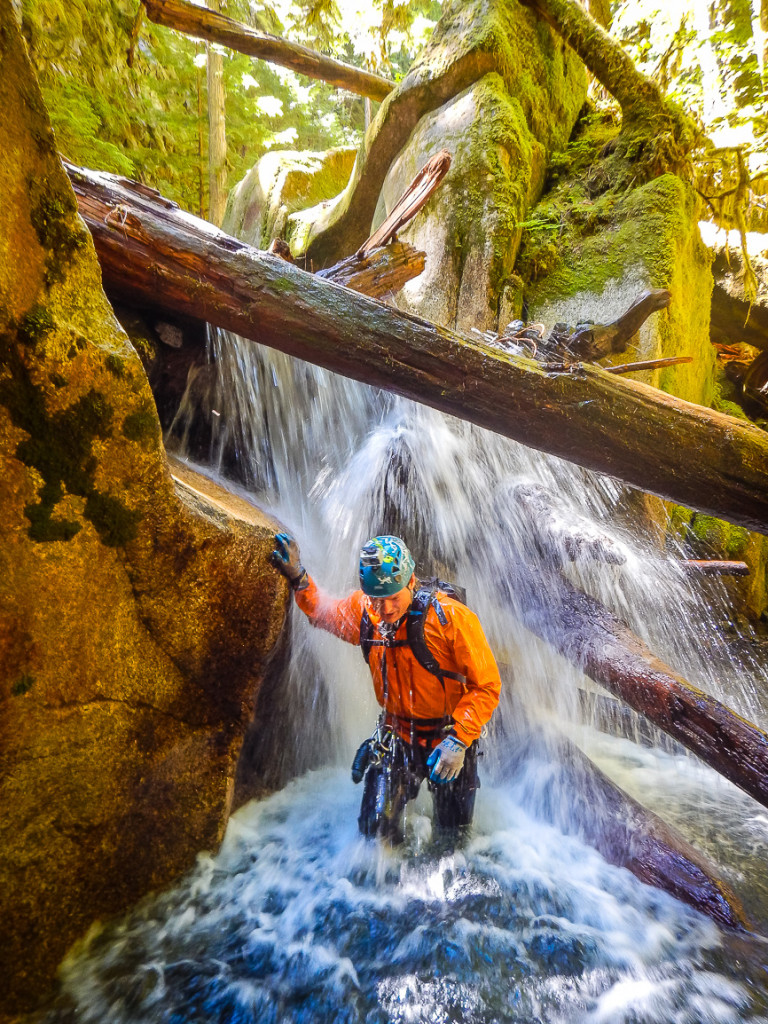A man wearing a helmet walks under the cascading water of a waterfall.