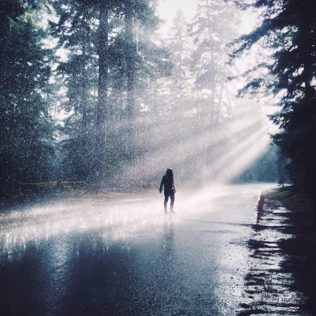A man stands in the middle of a road as the rain is caught by rays of sunlight.