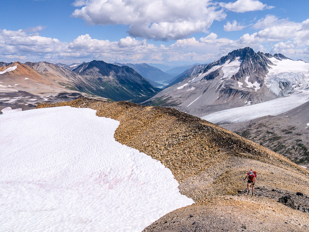 A hiker travels across a rocky terrain, with snow to his left and sweeping mountain ranges to his right.