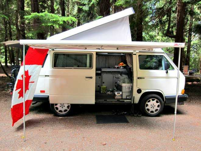 A beige camper van with a white awning and a Canadian flag.