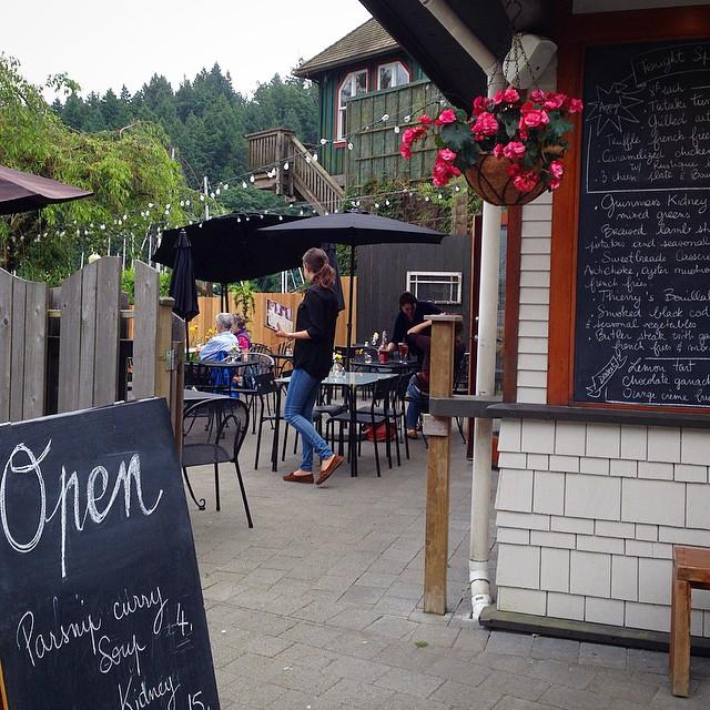 "Outdoor entrance to the patio of a restaurant with a chalkboard sign that says ""Open""."