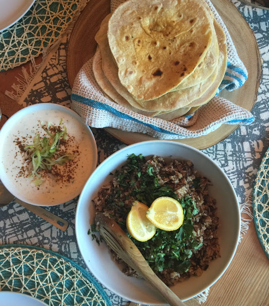 A flat lay of three beautifully prepared dishes of naan bread, wild rice, and a bowl of soup.