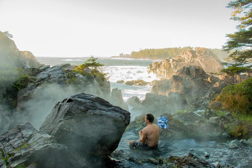 A young man sits in Clayoquot Sound's Hot Springs Cove, overlooking the Pacific Ocean.