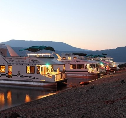 An array of houseboats anchored at the beach at sunset.