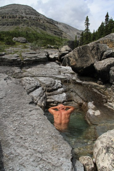 A man takes a dip in the clear waters of a creek.