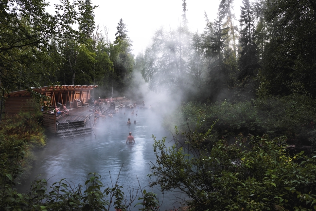 Groups of people take a dip in Liard River Hot Springs.