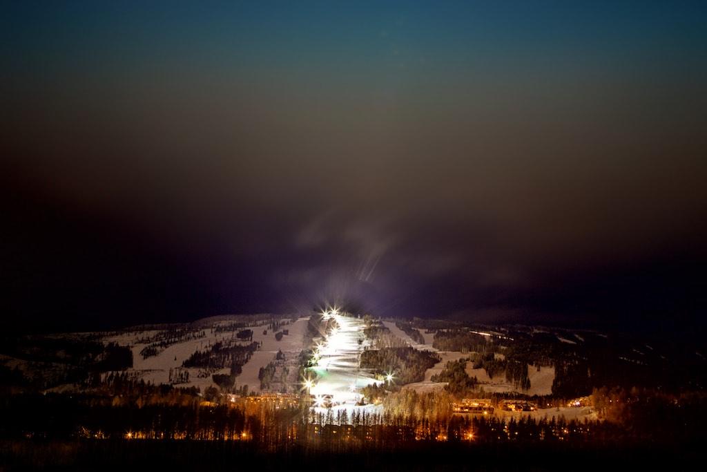 A brightly lit ski hill at night.