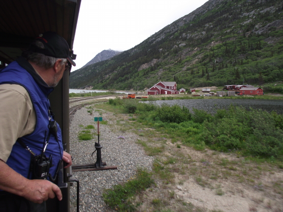 A man on a train looks back at a quiet valley dotted with red buildings.