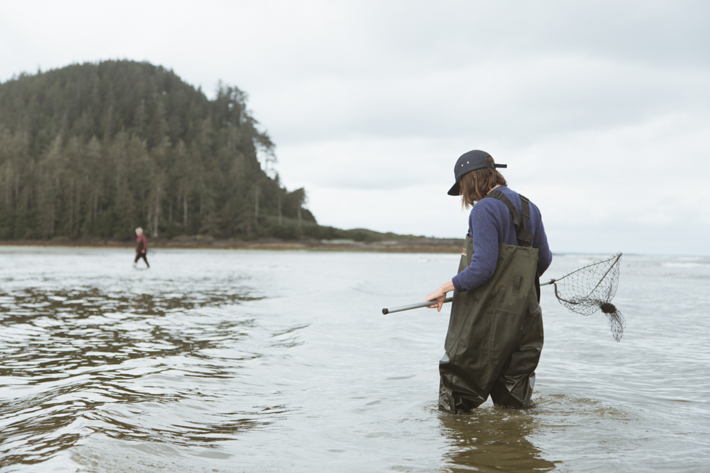 A woman wearing hip waders and carrying a small net stands in the ocean.