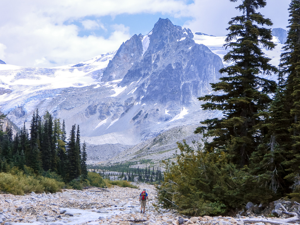 A hiker traverses a rocky trail, towards a sweeping snow-capped mountain range.