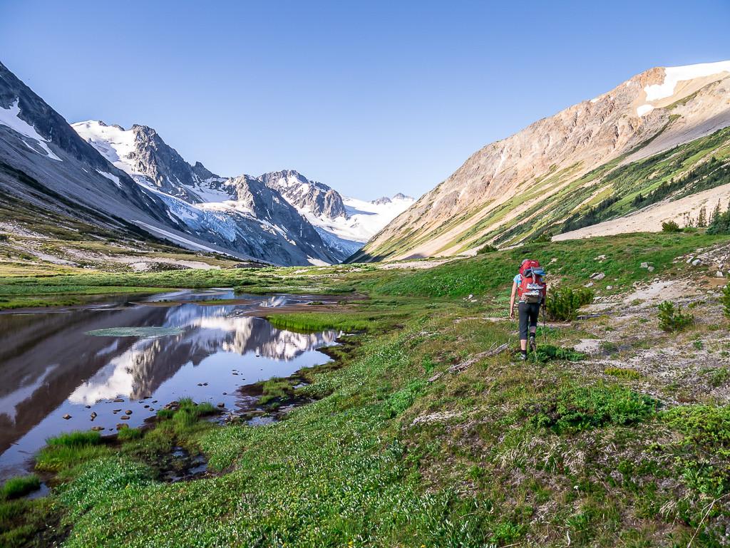 A hiker travels through a verdant valley, towards snowy mountains.