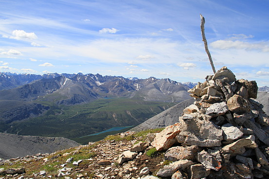 Standing on the peak of mountain, overlooking a lush valley and a snow-capped mountain range.